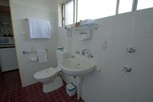 Accessible facilities include lowered sink, and rails adjacent to toilet.